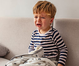 Toddler sitting on lounge with blanket crying