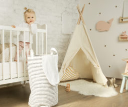 Baby standing in cot in nursery - feature