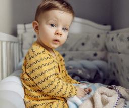 Toddler sitting up awake in cot