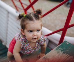 Toddler girl climbing playground equipment - feature