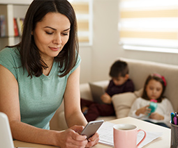 Mum on phone with kids in background on devices
