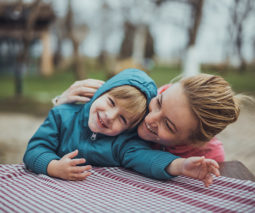 Young boy in jacket hugging mother in park - feature