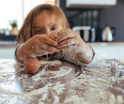 Toddler cracking eggs and cooking - feature