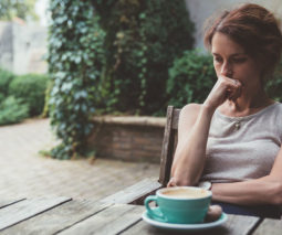 Woman drinking coffee outside alone - feature
