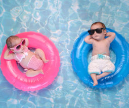 Pink girl and blue boy babies lying in pool - feature