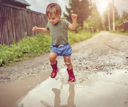 Toddler boy with gumboots jumping in puddle - feature