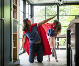 Mother playing with girl in kitchen wearing superhero capes - feature