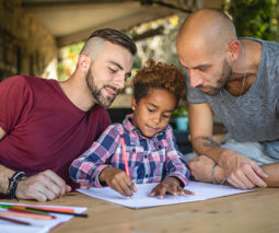 Same sex couple - two dads doing homework with their mixed race child