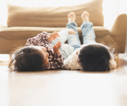 Children lying next to each other on the floor