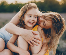 Young girl sitting outdoors being hugged by mother - feature