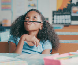 Young black girl at school desk playing with a pencil, not paying attention - feature