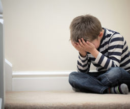 Upset boy sitting in time-out corner with head in his hands - feature