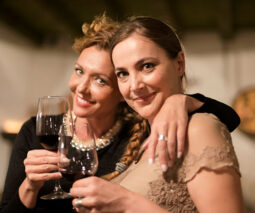 Two smiling women hugging and holding glasses of wine - feature