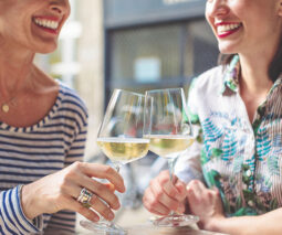 Two women smiling and clinking glasses of wine - feature