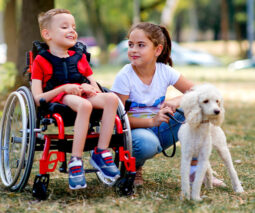 Boy in wheelchair with girl and dog